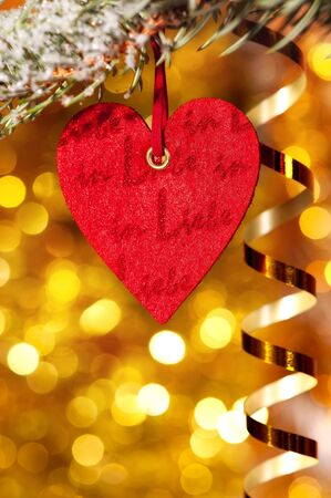 one heart on christmas fir tree branch and golden background photo