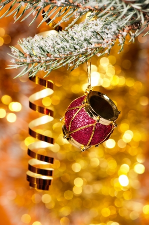 christmas drum on fir tree branch and golden background photo
