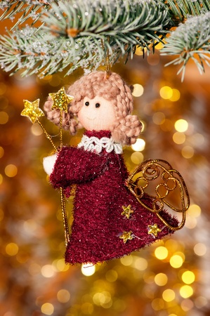 christmas angel on fir tree branch and golden background photo
