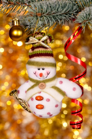 christmas snowman on fir tree branch and golden background photo