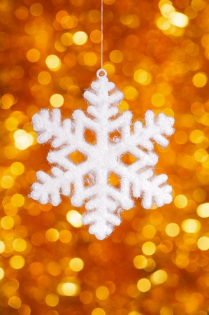 one big snowflake toy on golden bokeh background photo