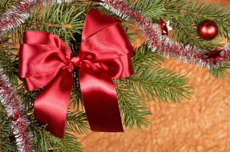 fir branches with red bow on golden background photo