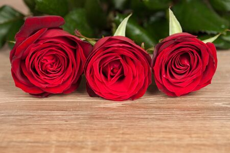 three red roses on wood Stock Photo - 18542421