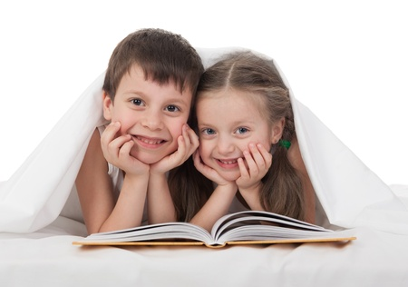children read a book in bed under the blanket photo