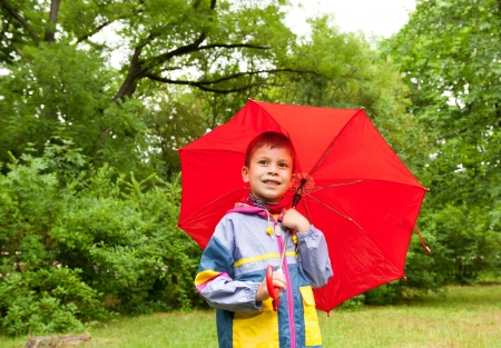 boy with red umbrella in park photo