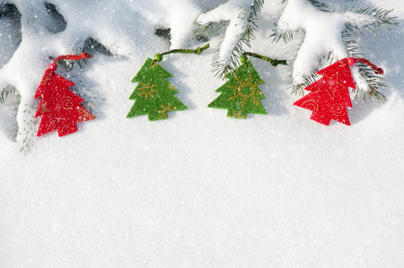 christmas red tree toys in snowfall on fir tree photo