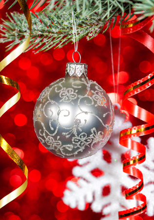 christmas ball on fir tree branch and red bokeh background photo