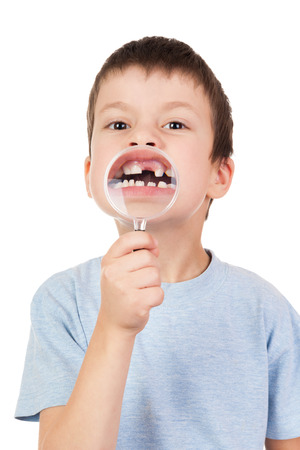 big smile: boy shows through a magnifying glass lost tooth Stock Photo