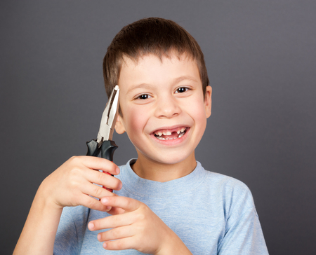 boy holds a lost tooth in the pliers photo