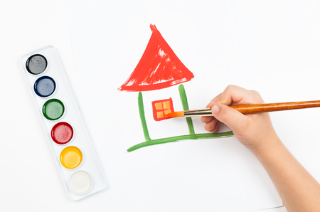 child draws house with watercolors photo