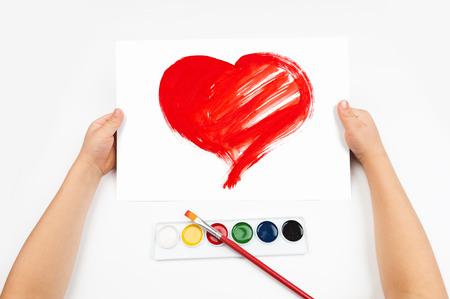 Child draws the heart watercolors photo