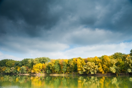 autumn forest, river and moody sky photo