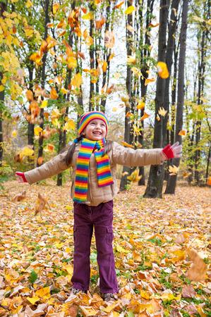 toss: girl in autumn park toss leaves