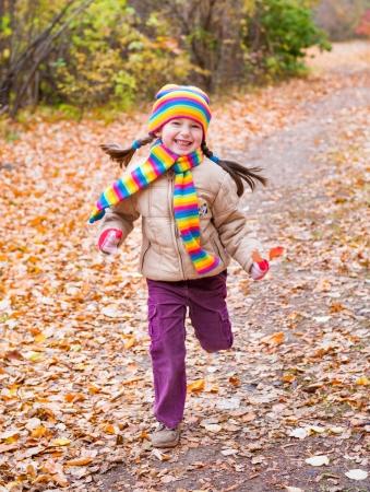 face in tree bark: girl runs in autumn park