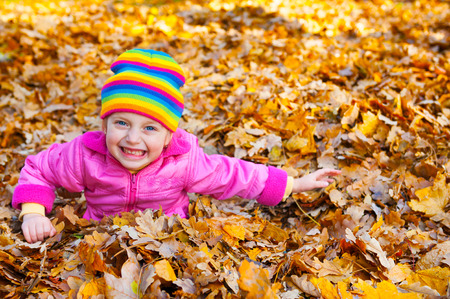 face in tree bark: girl lies on yellow leaves in autumn park
