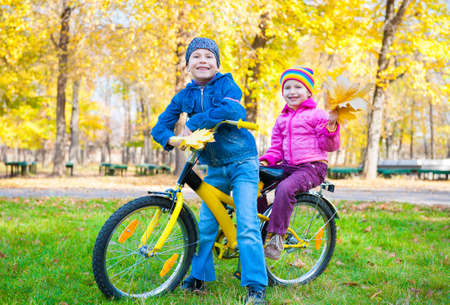 children on a bicycle in autumn park photo