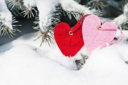 red hearts toy in snowfall on fir tree photo