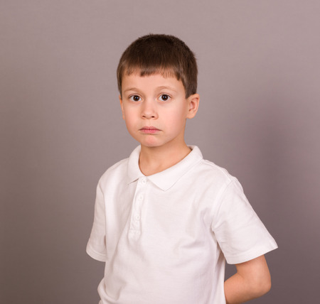 crying boy: sad boy on grey Stock Photo