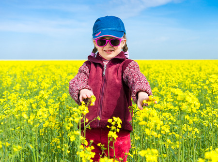 girl in a yellow field of rapeseed flowers. photo