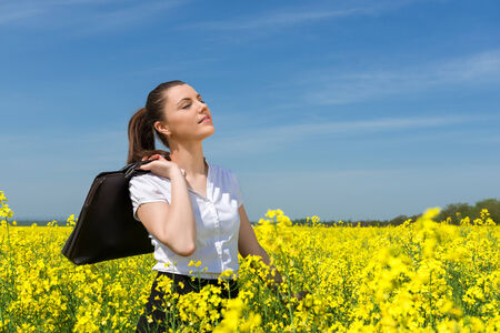 business woman with briefcase at the yellow flower field photo