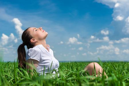 portrait of beautiful woman relaxing on field photo