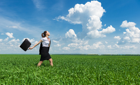 girl with a briefcase walking on the grass photo