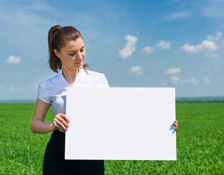 girl with blank billboard on green field Stock Photo - 28406429