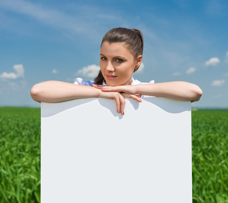 girl with blank billboard on green field photo