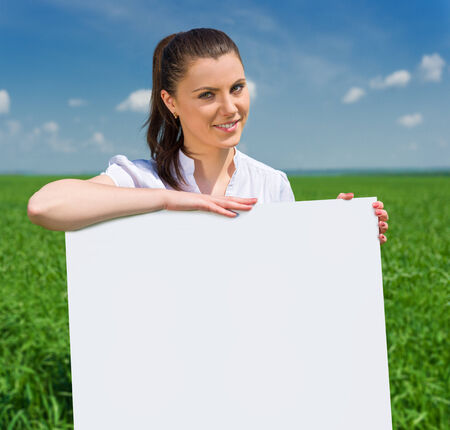 girl with blank billboard on green field photo