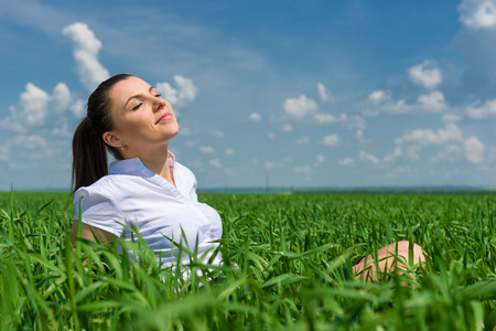 portrait of beautiful girl relaxing on field photo