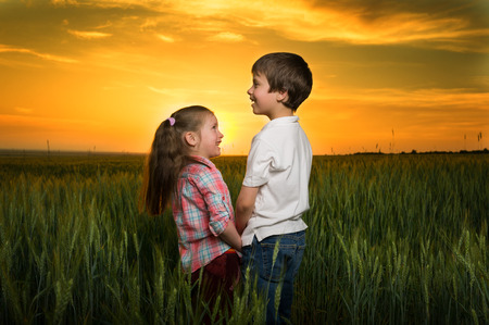 children in a field at sunset photo