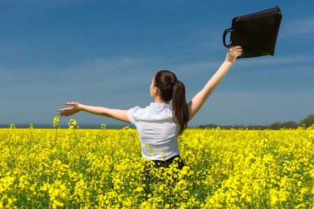 woman with a briefcase on yellow flower field photo