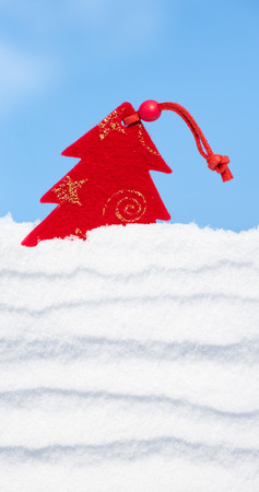 christmas tree toy in snow on sky background photo