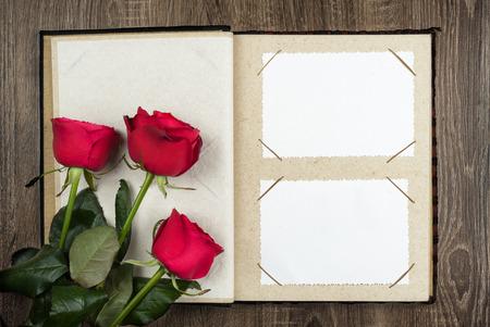 photo album and roses on wood background photo