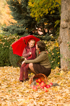 woman and little girl in autumn park with apple basket and umbrella photo