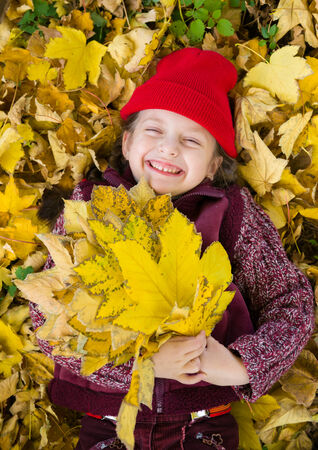 little girl in autumn park lying on leaves photo