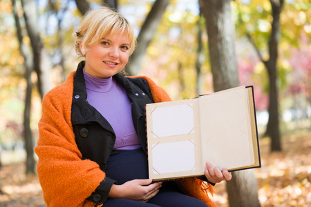 pregnant woman with blank photo album in autumn park photo