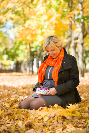 pregnant woman with baby shoes in autumn park photo