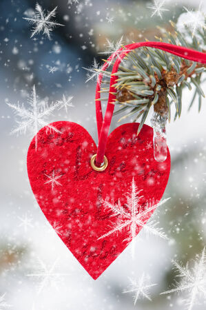red heart toy with snowflakes on fir tree photo