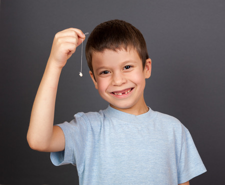 boy with lost tooth on a thread Stock Photo