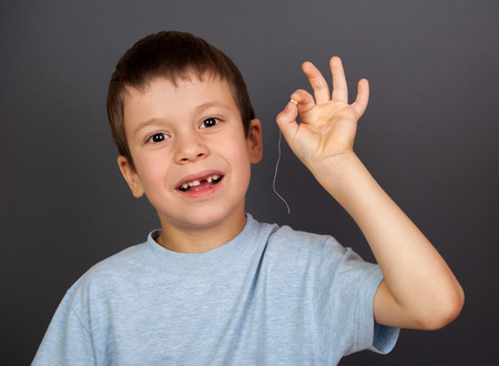 self operation: boy with lost tooth on a  thread Stock Photo