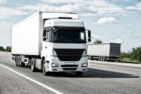 수송: 도로에 흰색 트럭. 화물 운송