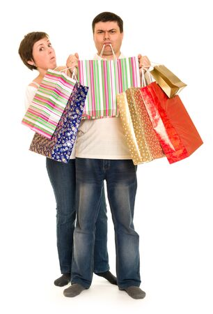 henpecked: man hold in teeth shopping bags and woman
