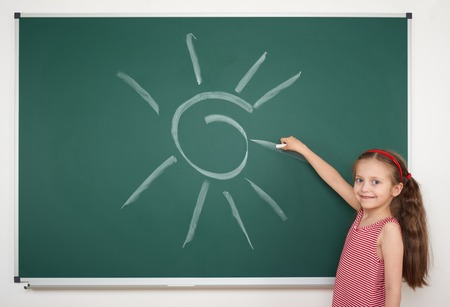 girl young: girl drawing sun by white chalk on school board