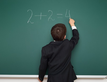 black board: School boy solve math on the school board Stock Photo
