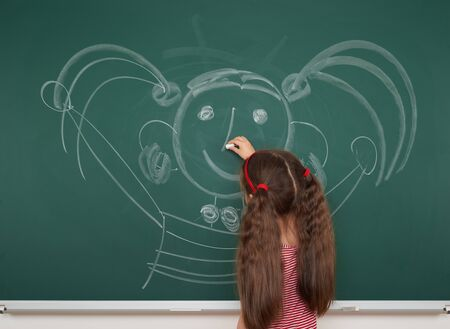 children education: girl drawing faces on the school board