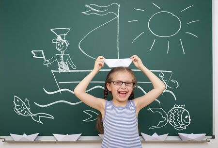 pizarron: girl with origami ship drawing on school board