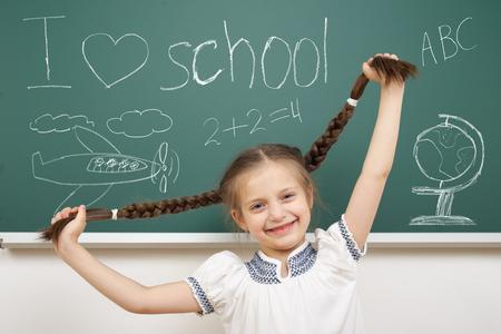 dessin enfants: fille avec objet de dessin en queue de cochon � bord de l'�cole
