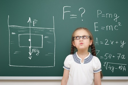 to gravity: girl drawing physical phenomenon gravity on school board Stock Photo