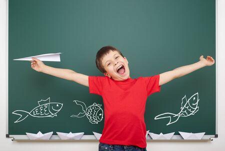 school fish: boy drawing fish on school board